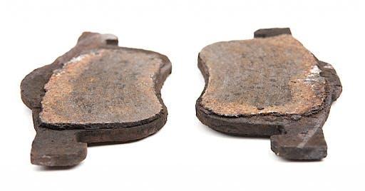 A set of worn out brake pads