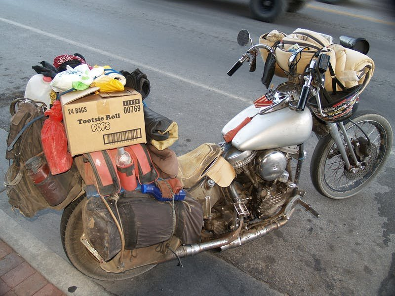a silver motorcycle overfilled with luggage