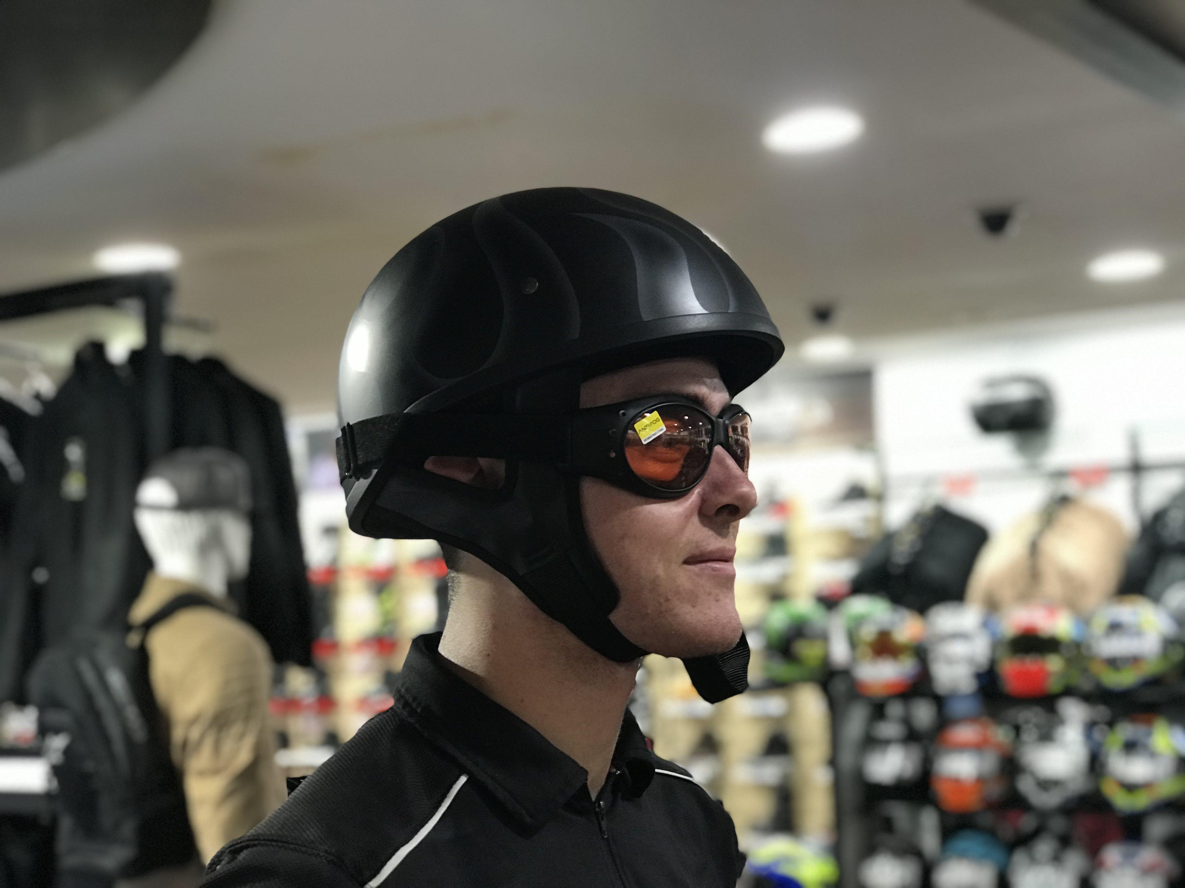Half face helmet with orange goggles on a man