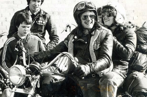 Old photograph in black and white of a man and woman on a motorcycle