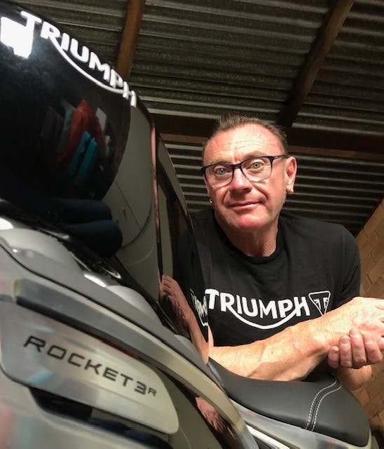 Self timer selfie of a man leaning on the seat of a Triumph Rocket 3 R